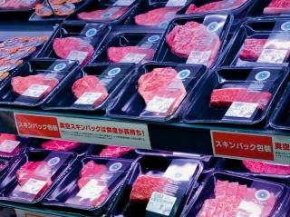 """「真空スキンパック」包装の商品が並ぶダイエーの精肉売り場(左)。チラシには大きな文字で「鮮度長持ち」と記載し、消費期限の長さをアピールする<br><span class=""""fontSizeS"""">(写真:ダイエー)</span>"""