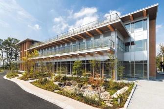 """2019年10月21日に完成した住友林業筑波研究所の新研究棟は、「W350計画」の開発拠点と位置づけられている(左)。新研究棟の壁柱は縦横1200㎜、厚さ300㎜の単板積層材(LVL)のブロックを積み上げ、その中に鋼棒を貫くオリジナルポストテンション構造を採用。W350計画の実現に向けて、このような木を""""活かす""""技術開発を推し進めていく<br><span class=""""fontSizeS"""">(写真提供:住友林業)</span>"""