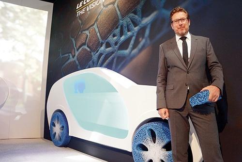 「Movin'On2018」のミシュランのブースでは、持続可能なタイヤのコンセプトモデル「ビジョンコンセプト」が展示されていた(写真の青いタイヤ)。ミシュラン・コーポレート・サイエンティフィック・イノベーション・コミュニケーション・ディレクターのシリル・ロジェ氏は、タイヤ原料を持続可能な原料に切り替えることで、将来の原料価格の高騰に備えると説明する