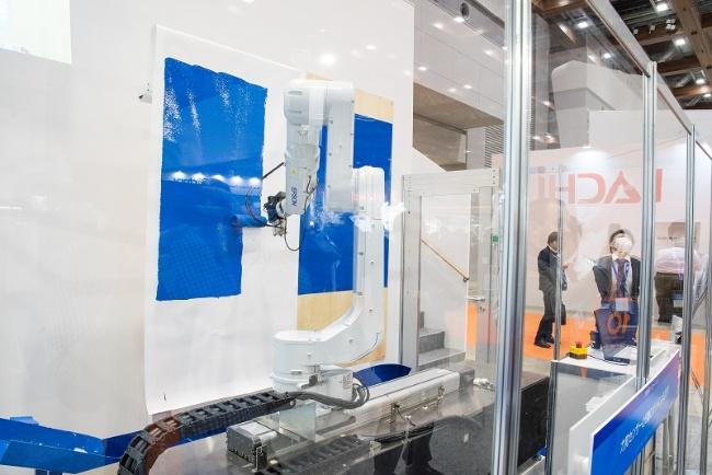 図5 力覚センサーでローラを適切な力で壁に押し当てながら塗装するロボット