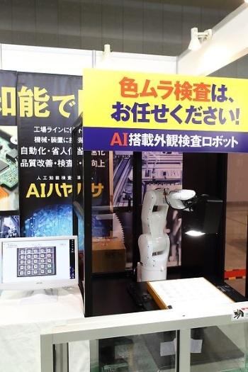 ミラック光学が展示した色ムラ検査装置「AIハヤブサ」(写真右側)