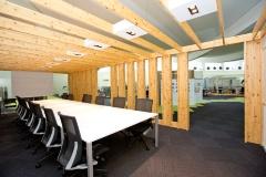 2階フロアの中心に置かれた「センター」。会議の様子・雰囲気を職員や来庁者も感じ取ることができる半開放的な会議室だ。右写真左側の直方体の工作物は空調機の周囲を木材などで囲んでホワイトボードを取り付けたもの。2階フロア中央部の空調期は3台とも同様にホワイトボードが取り付けられ、「プレゼンテーション」と名付けたスペースとなっている(写真:江田 健一)