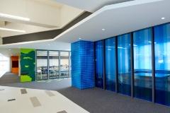 写真左は2階の「キャンプ」。机の組み合わせによって、少人数から多人数まで柔軟に対応でき、市民や職員の情報交換の場になっている。写真右は1階の多目的会議室「地域協働スペース」は室ごとにカラフルに色分けされている(写真:江田 健一)