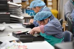 """<div class=""""clearBoth""""> </div>包装作業は、雇用契約を結ばずに就労機会を提供する就労継続支援B型事業として「コンチェルト」事業に受け継がれている。ポップな音楽が流れる事業所で箱詰め作業をする(写真:大槻 純一)"""