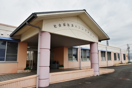 1999年に開所した「シンフォニー」は、授産施設「コンチェルト」(上右)とデイサービスセンター「ファンタジア」(上左)を行う全国初の合築施設となった。その中には児童デイサービス事業「ま~ち♪」も行っている(中)。シンフォニーの建物(下)(写真:大槻 純一、給食写真はシンフォニー提供)