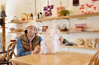 """<div style=""""clear:both;""""> </div>東京から来た梅田さん(左)は、元・保育士。人形を作るのが趣味で、共有スぺースにあるショップ「ま~る」でも売っている。「お孫さんへのプレゼントで買ってくれる人がいて、とてもうれしいですね」と語る。地域の人が作った洋服(右)や入居者の衣類、雑貨などもここでリサイクルとして出されている。売上金がまとまったら、福島の子どもの健康回復のための保養プロジェクト団体へ寄付している。(写真:大槻純一)"""