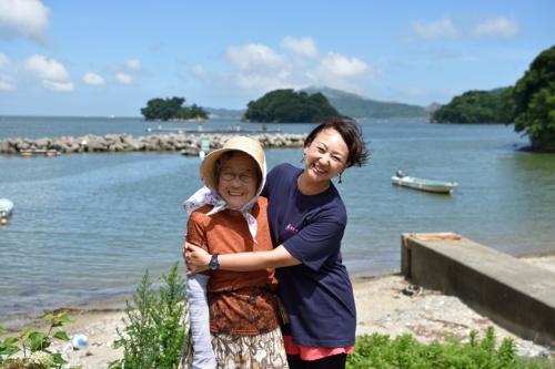 (上)無人島にカヤックで渡るツアーも人気だ。(下)カヤック小屋の近くに住む女性と。浜のみんなから「きくちゃん」「きくちゃん」と声をかけられる江崎さん(写真:大槻純一)