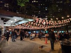 マンハッタンのマディソン・スクエア・パーク内で午前7時半から午後11時まで開いているハンバーガー屋(Shake Store1号店)(左:夜の様子、右:昼間の様子)。2001年に公園のコンセッションとしてホットドッグカートとして始まり、その人気によって、現在では世界に拡散した(資料:島田智里)