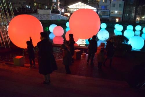 チームラボの作品「呼応する球体のゆらめく川」。護岸の公園に設置された球体を叩くと、球体の光の色が変化し、周りの球体も同じ色へと変わっていった(写真:大井 智子)