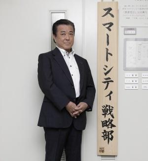 坪田 知巳氏。スマートシティ戦略部の入り口にある看板の前で(写真:行友 重治)