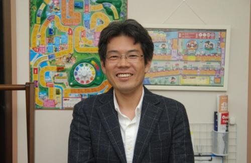 まちあそびリアル人生ゲームの発案者の田中寛氏。出雲市役所の職員であり、リアル人生ゲームの運営などを手掛けるNPO法人出雲まちあそび研究所の副理事長でもある(写真:佐保 圭)