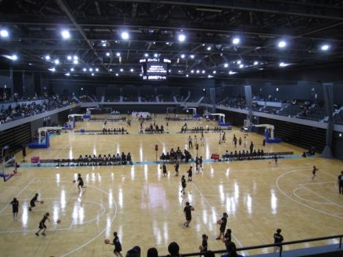 プレイベントでミニバスケット大会を開催中のメインアリーナ。2階の観客席は室内ランニングコースを兼ねている。4面ビジョンの上下にリングビジョンを備えたセンタービジョンは、イベントを盛り上げる装置だ(写真:由利本荘市)