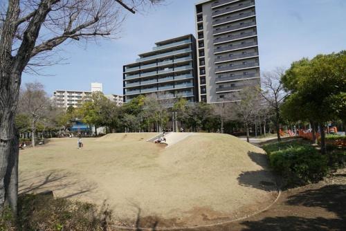 リニューアル後の竹園西広場公園(撮影は2021年4月)。すべり台付きの小山を築き、子どもたちが工夫して遊べるようにした。土壌を改良して植えた芝生が夏季には青々と茂る。公園の小山の奥のマンションがフージャースが開発した「デュオヒルズつくばセンチュリー」(写真:日経BP 総合研究所)