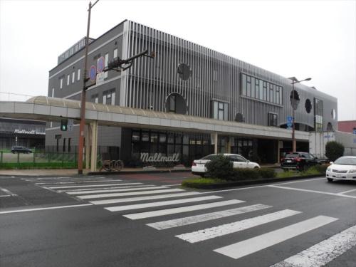 中心市街地中核施設「Mallmall(まるまる)」の新築建物。1階部分はガラス張りのオープンなつくり。左奥に見えているのが、図書館を核とする施設に転用された既存建物(写真:茂木俊輔)