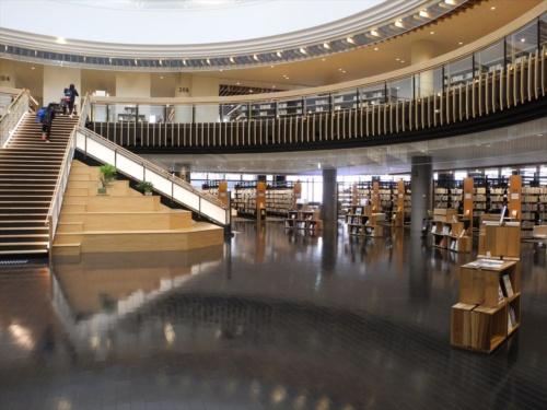 図書館吹き抜け部分の1階。右手に積み上げられた木製の箱は、マルシェの木箱をモチーフに製作された木箱架。この図書館では書架として多用されている(写真:茂木俊輔)