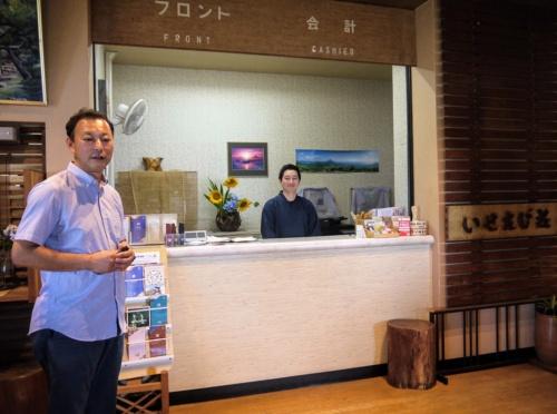 いせえび荘フロントで。左が加藤潤氏、フロントに立っているのは西村正幸氏の後を継いでいせえび荘を運営する西村徹氏(写真:萩原詩子)