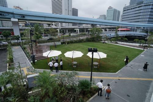 727m2の芝生広場にはパラソルを設置。ステージも設けられ、音楽イベントやパーティーを開催できる。すでに映画の野外上映会や地元サークルの発表会などが行われている(写真:日経BP総研)