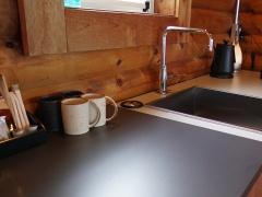 管理棟の2階 (左写真:赤坂 麻実)には、打ち合わせをしたり、雨天の際にバーベキューをしたりできるスペースが。コスモスイニシアは、ワーケーション利用にも対応したい考え。キャビンやテントには地元・笠間焼のコーヒーカップが用意されている(上写真:日経BP)