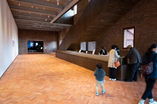エントランスを入って右手にある受付カウンター。左の壁面は市民ギャラリーとして利用可能(写真:村上 昭浩)