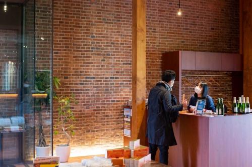 旧建物のレンガ壁を活かしたカフェ・ショップ棟。店内で醸造した限定シードルが楽しめる(写真:村上 昭浩)