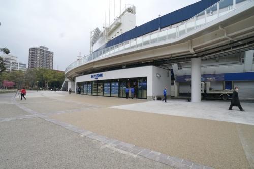 Yデッキの下に横浜ベイスターズのオフィシャルショップ「BAYSTORE PARK」を設置。そのほか、Yデッキ軒下の開放的な空間でバザーなど各種イベントを開催するなどして、敷地の横浜公園と連動した賑わい創出も見込む(写真:日経BP)