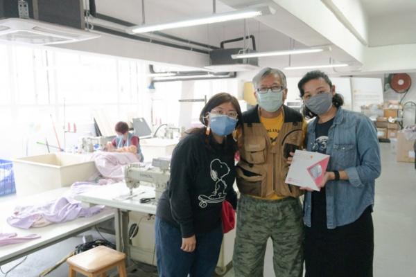 「HK Mask」を共に開発・製造する、香港郊外の工業地帯にあるSew on Studioで、同スタジオ共同創業者ミユキ・チェン氏とウィンソム・ロック氏に囲まれた鄺博士