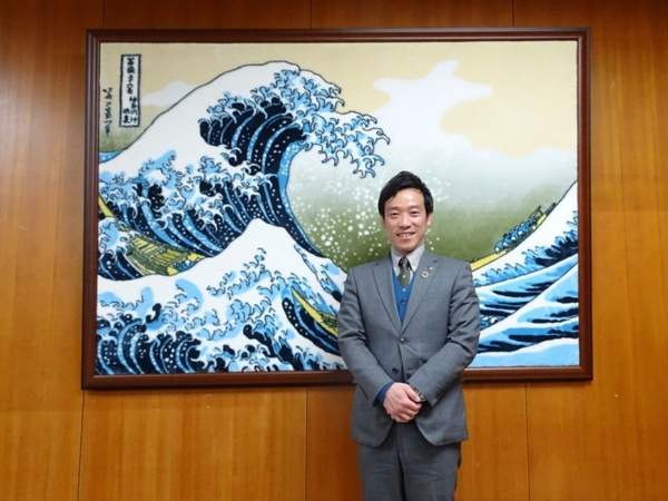南出賢一市長。背景の北斎の複製画は同市の特産品である毛布でつくられたもの(写真:赤坂 麻実)