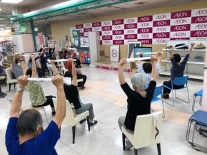 ラジオ体操(写真左)および高岡市が開発した健康体操(写真右)で体を動かす参加者。市の健康体操は、高齢者向きに椅子に座ってもできるようになっている。(写真:2点ともイオンリテール)