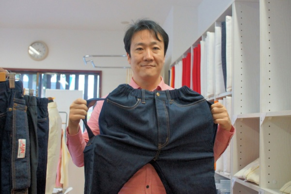 エナジーフロント社長の上田剛慈氏。岡山県倉敷市の美観地区の一角にある「AUN SHOP」店内で。手に持つのが「リフトアシストジーンズ」(写真:筆者が撮影)