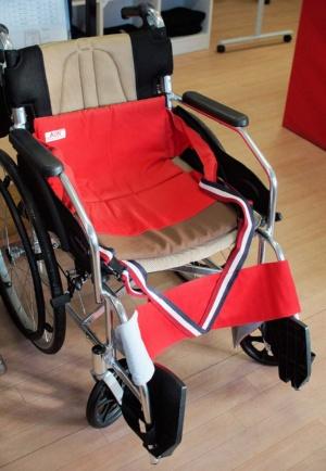 リフトアシストジーンズの原型となった移乗機能付き座イスの「リフティピーヴォ」(赤色のもの)。写真では車椅子に乗せている。色や素材に配慮し、部屋を明るくするようなデザインにしたという。筆者はこちらで上田氏を相手に移乗介助を初めて試したが、難なくこなせた(写真:筆者が撮影)