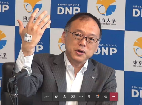 大日本印刷 研究開発センター 部長の前田博己氏。右手の甲にセンサーを搭載したスキンディスプレーを貼り付けている(写真:オンライン記者会見の画面キャプチャー)