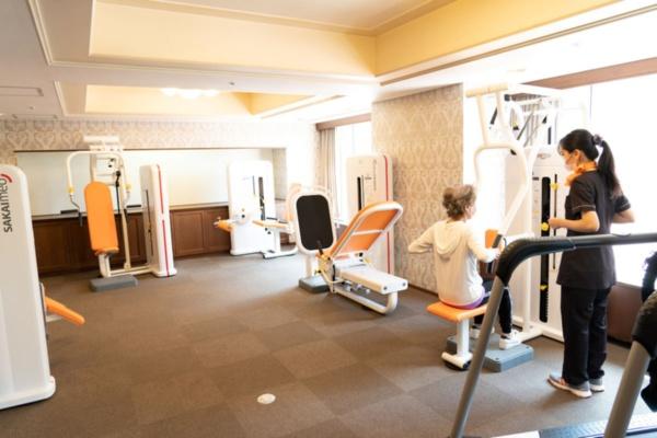 ゆったりとしたトレーニングルームに、酒井医療のパワーリハビリ用機器6機種を用意する。一般的なトレーニングマシンと見た目は似ているが、負荷が軽いという特徴を持つ。筋肥大ではなく、関節の柔軟性や関節可動域の回復を目的とする。軽いリズミカルな動きで、弱った全身の神経と筋肉を再び活性化させるという(撮影:大亀 京助)