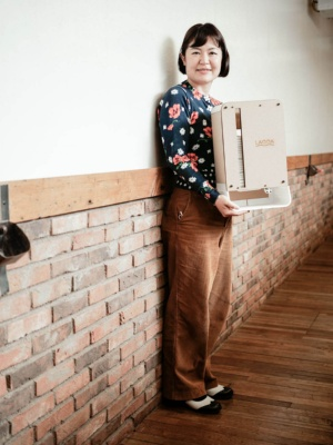 わたしの暮らし研究所 代表 沢田直美氏。持っているのは、生理用ナプキンディスペンサー「LAQDA」。3Dプリンターやレーザーカッターを使って加工した部品を使用しており、ユーザーが組み立てることも可能(撮影:加藤 康)