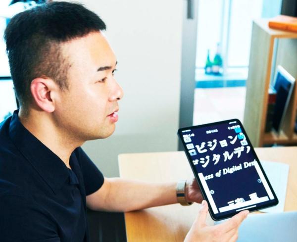 拡大・縮小が容易なタブレット端末で閲覧する方が、ルーペや拡大読書器などで拡大するより視認性や操作性は向上。(写真:寺田 拓真)