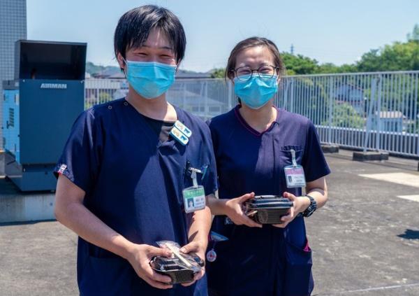 ドローン配送された牛丼を受け取る医療スタッフ(出所:プレスリリース、以下同)