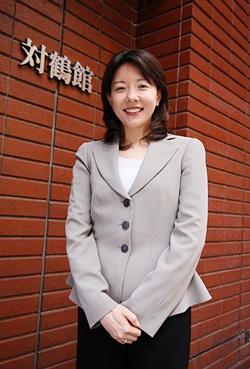 亀岡商会 常務取締役 亀岡幸子さん。対鶴館ビルの赤レンガの前で(写真:山田愼二、以下同)