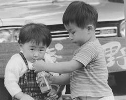 幼少の頃の浅野さん(左)。浅野屋軽井沢旧道店の前で兄と