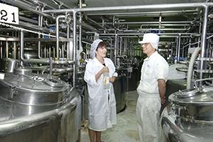 工場内の調合室。果汁、砂糖、香料などをタンクで混合する。担当者と話す田中社長(写真:いずもと けい)