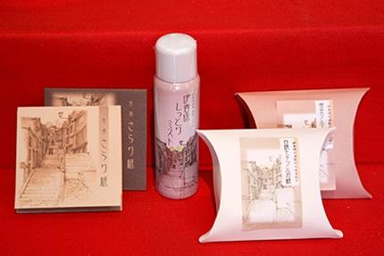 伊香保おかめ堂本舗の商品。左からあぶら取り紙「香湯さらり紙」、スプレータイプの化粧水「伊香保しっとりミスト」、そして2種類の石鹸「黄金ツルスベ石鹸」と「白銀モチプル石鹸」
