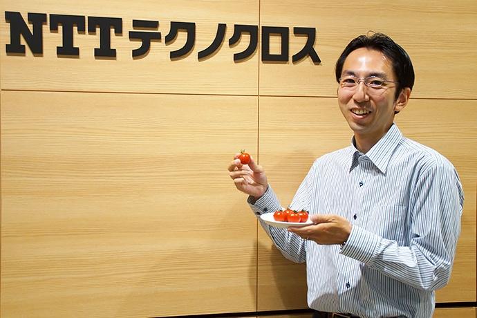 NTTテクノクロスの酒井歩氏。手に持つのはレーザー技術で測定し、かつキャンペーンでも扱っているミニトマトの「あまばんか」