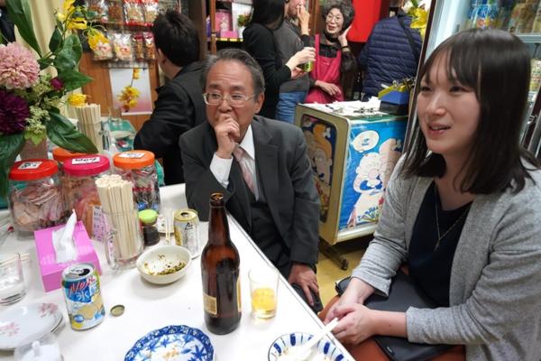 北九州角打ち文化研究会は、酒屋の売り場に置かれたテーブルでお酒を飲みながら会合する。中央は角文研会長の吉田茂人さん、右は著者の塩見なゆ(写真:ひとまち結び編集部)