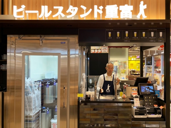 ビールスタンド重富。JR広島駅「ekie KITCHEN」のイートインコーナー「エキエスタンド」前にある。カウンターに立つのが重富寛さんである(写真:筆者、以下同)