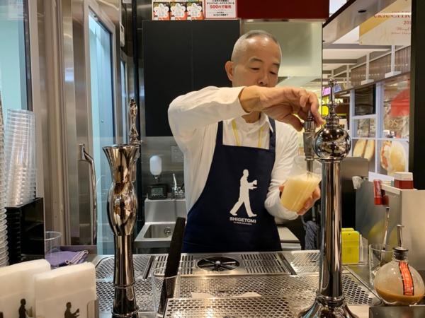 昭和のサーバーからビールを一気に注ぐ重富さん
