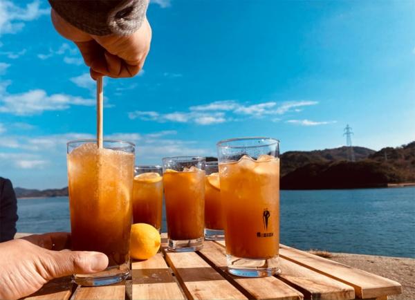 岡さんがFacebookにアップした写真の1枚。瀬戸内の青空をバックにしたレモンやカクテルの写真が目を引く