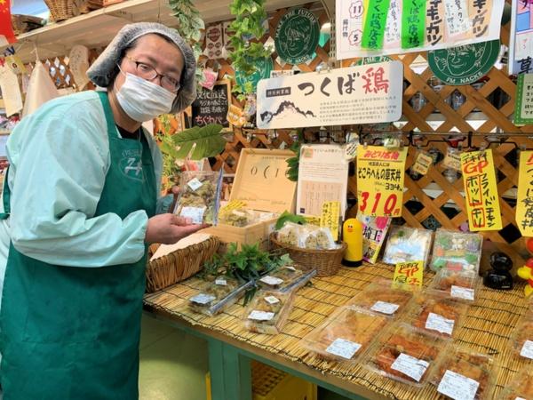 """みどりスーパー惣菜部の河内みどりさん。河内さんが「""""爆誕""""商品」と呼ぶ「そこらへんの草天丼」の売り場の前で(写真:筆者)"""