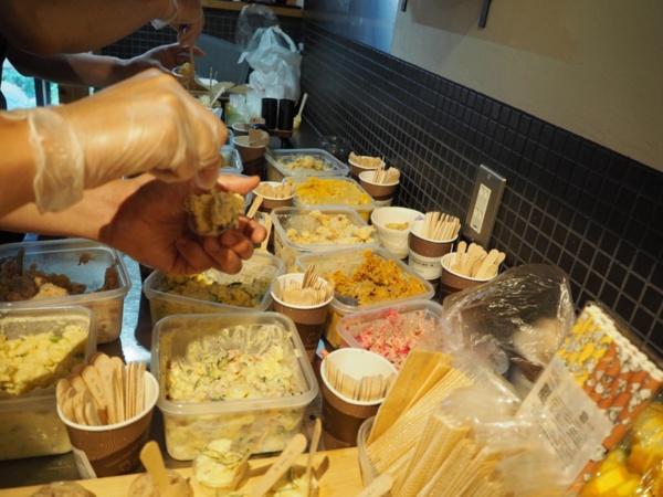 厨房で準備をするスタッフはタッパーで集められたポテサラを小さなカップに分け、盛り合わせにする。カップに添えられた木製のスプーンには店名が印字されている。感染対策にも細心の注意を払う(写真撮影:楠原陽子さん)