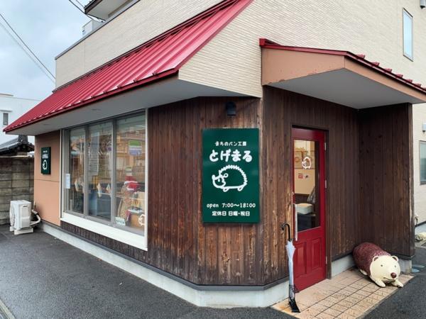「とげまる」の外観。近くに国道9号・山口バイパスが走り、小売、飲食など大型のロードサイト店舗も多い。ドアの横で出迎えてくれるのはマスコットキャラのハリネズミ「とげまる」くん