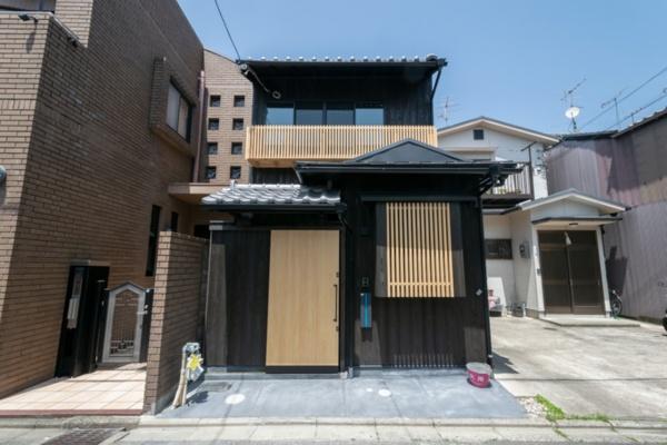 「道楽町家(DO-RAKU MACHIYA)」南側外観。木製引き戸の奥に玄関へのアプローチが続く(写真提供:八清)