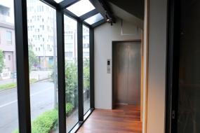 エレベーター前はガラス張りの通路(写真:青木 桂子)
