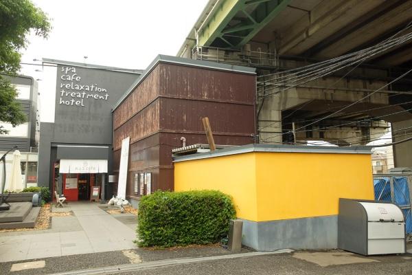 さいたま市北区にある「おふろcafé utatane」の外観。建物の上部に見えるのはJR東日本の鉄道高架橋(写真:塩谷歩波)